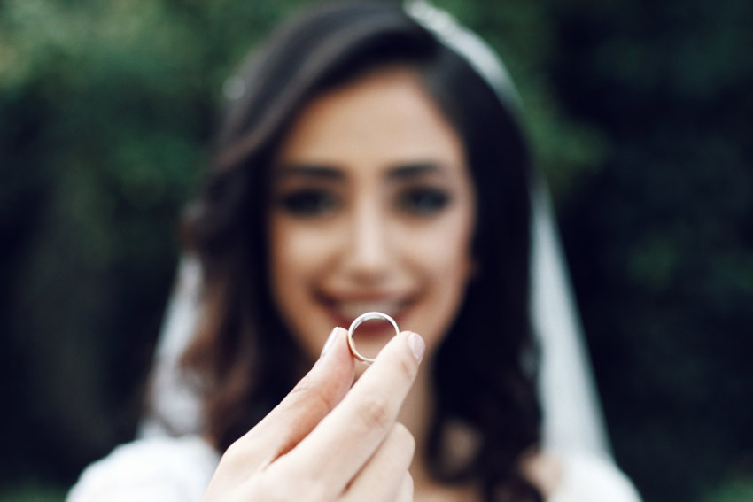 wedding day bride holding up ring to camera front on facing